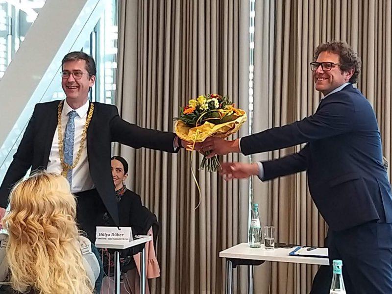 Oberbürgermeister Christian Schuchardt überreicht dem neuen Klimabürgermeister Martin Heilig einen Blumenstrauß