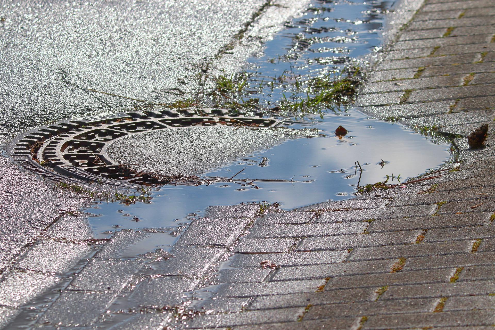 Regenwasser fließt in Gullideckel